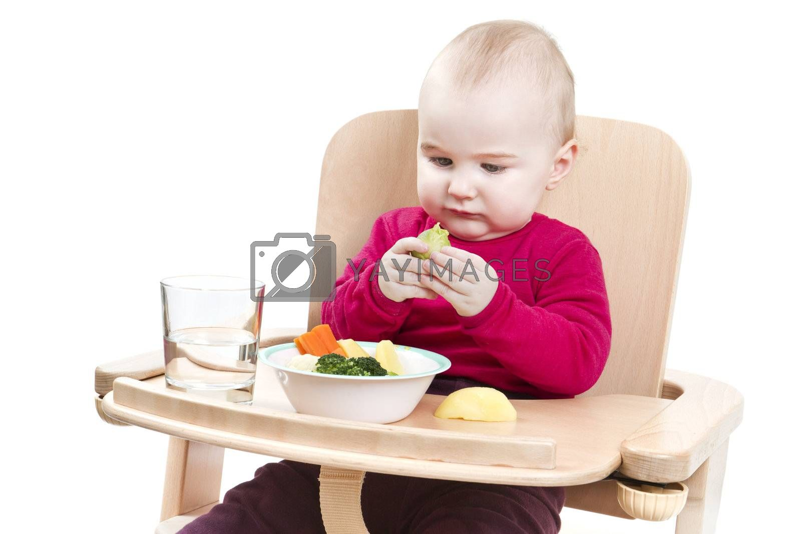 young child in red shirt eating vegetables in wooden high chair.