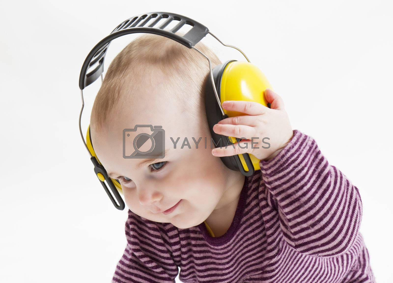 young satisfied child with yellow ear protector. hand is putting off the earmuffs