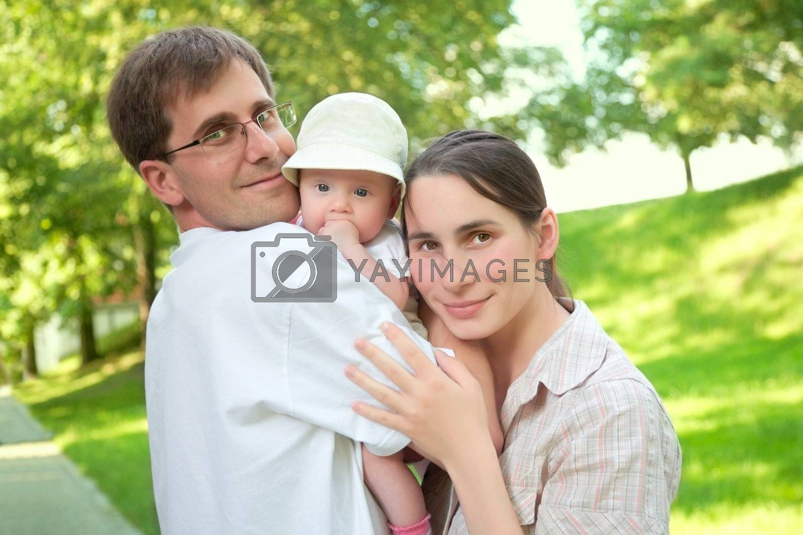 smiling young family with a baby