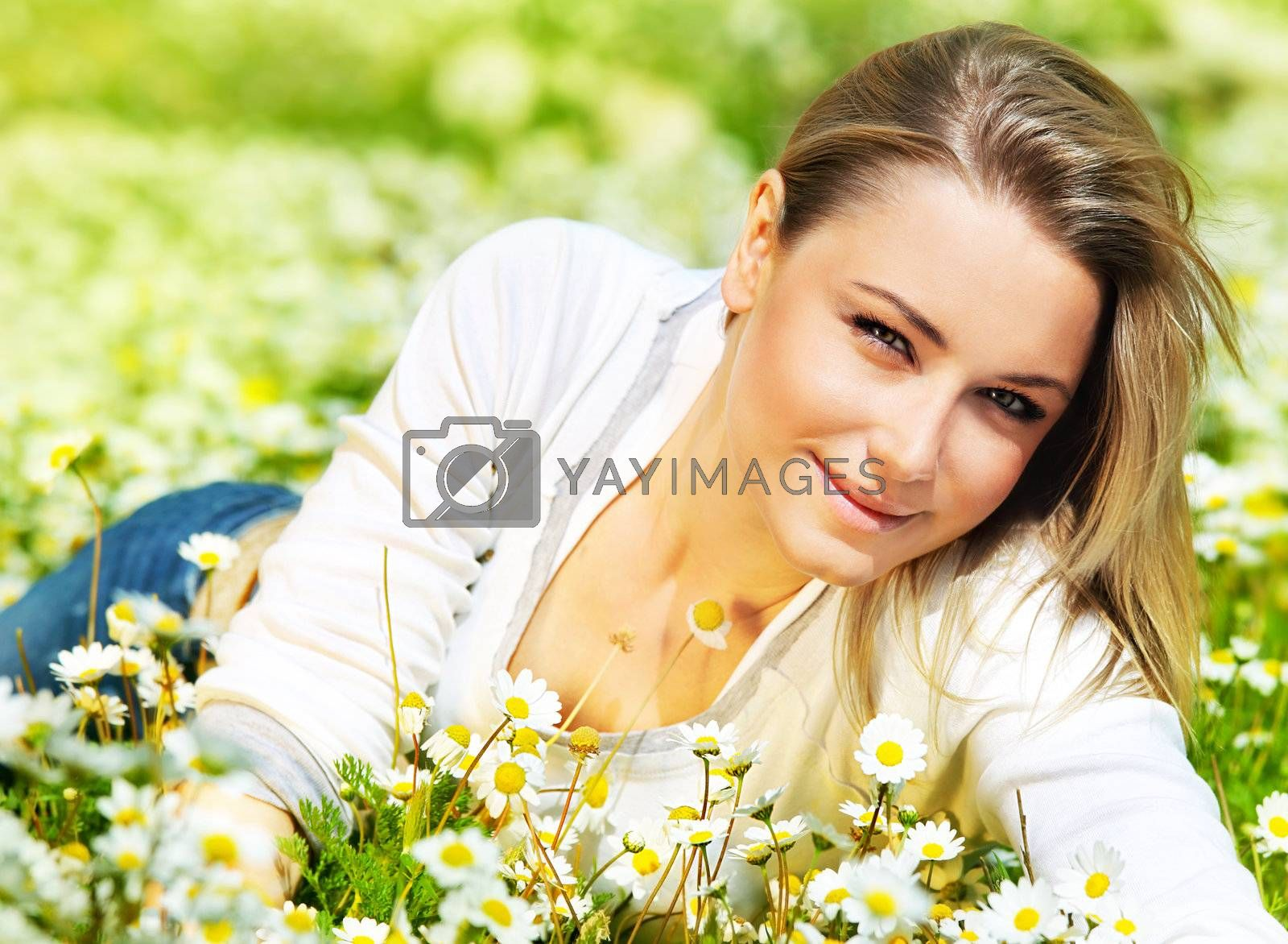 Beautiful female laying on the flower field