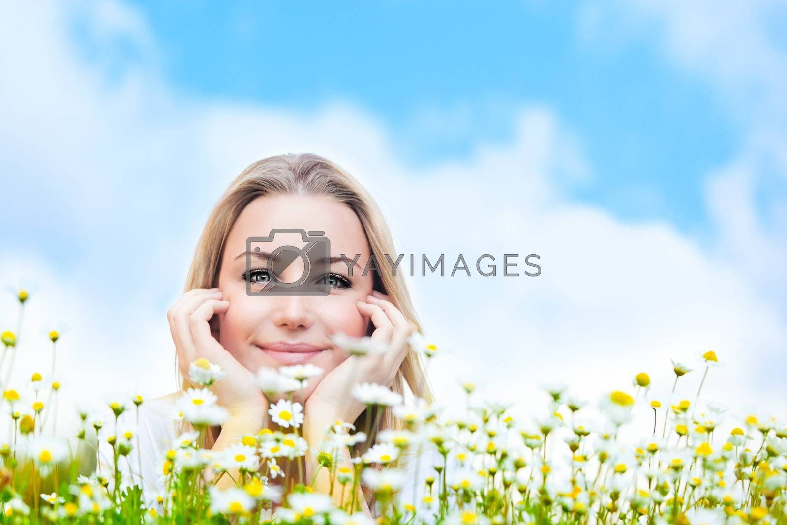 Happy young female lying on the flower field, over blue cloudy sky, with copyspace, leisure, fun and wellness concept