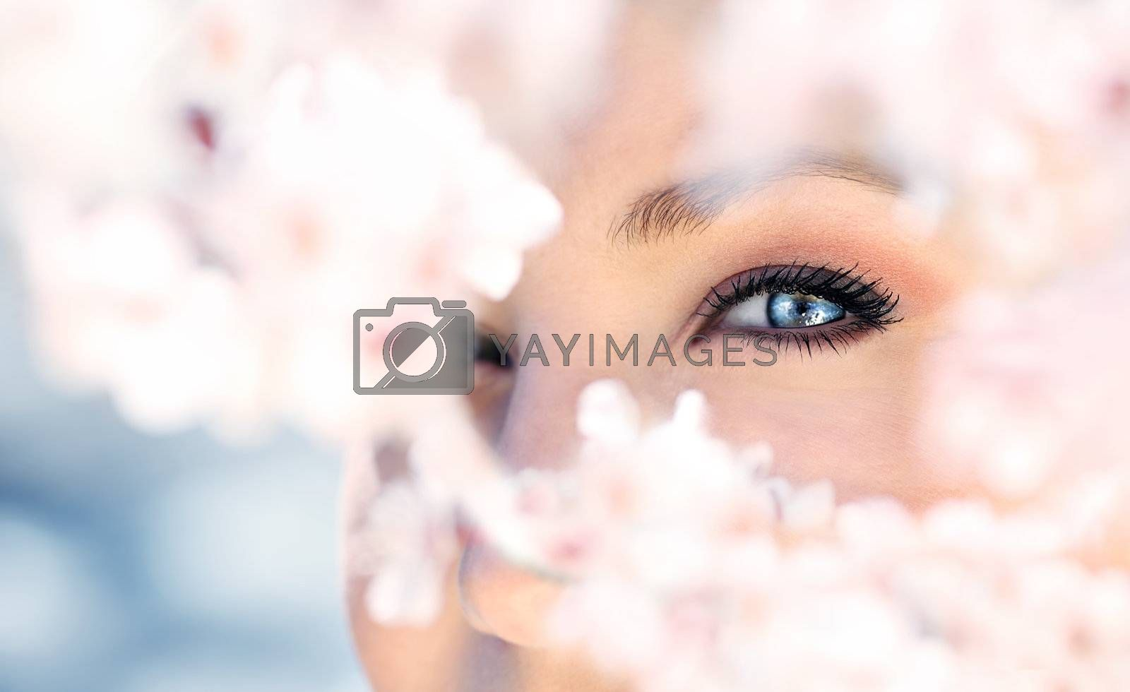 Beautiful abstract blue eye surrounded with fresh flowers, macro portrait outdoor
