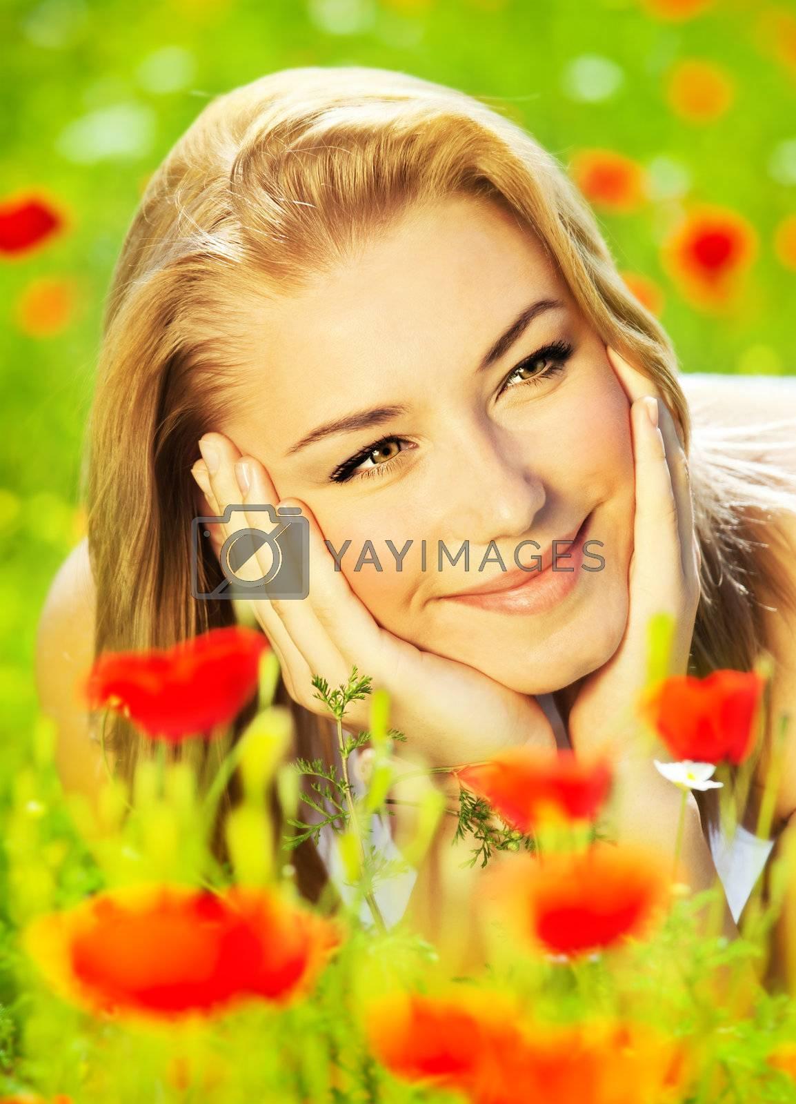 Lovely happy female closeup portrait, lying down in the poppy flower field, enjoying nature, summertime leisure concept