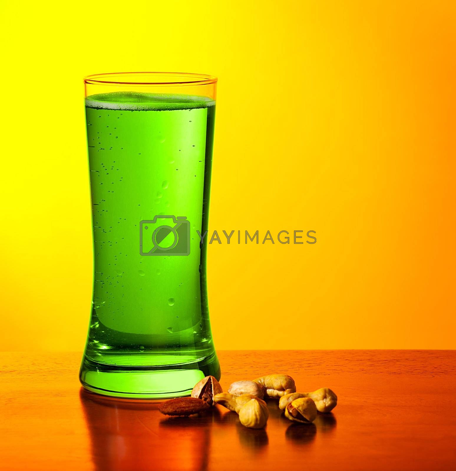 Glass of cold green Irish beer drink isolated on yellow warm background, festival of beer, traditional alcohol for st.Patrick's day holiday celebration, lucky clover beverage, studio food still life