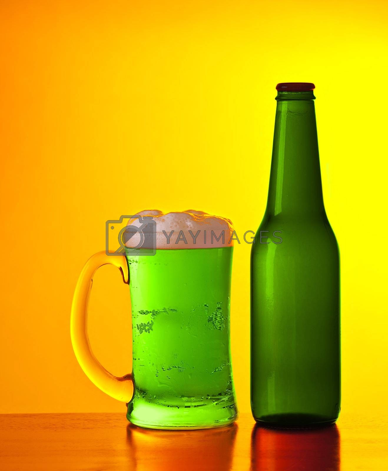 Glass of cold green Irish beer drink isolated on yellow warm background, festival of beer, traditional alcohol for st.Patrick's day holiday celebration, lucky clover beverage, studio still life