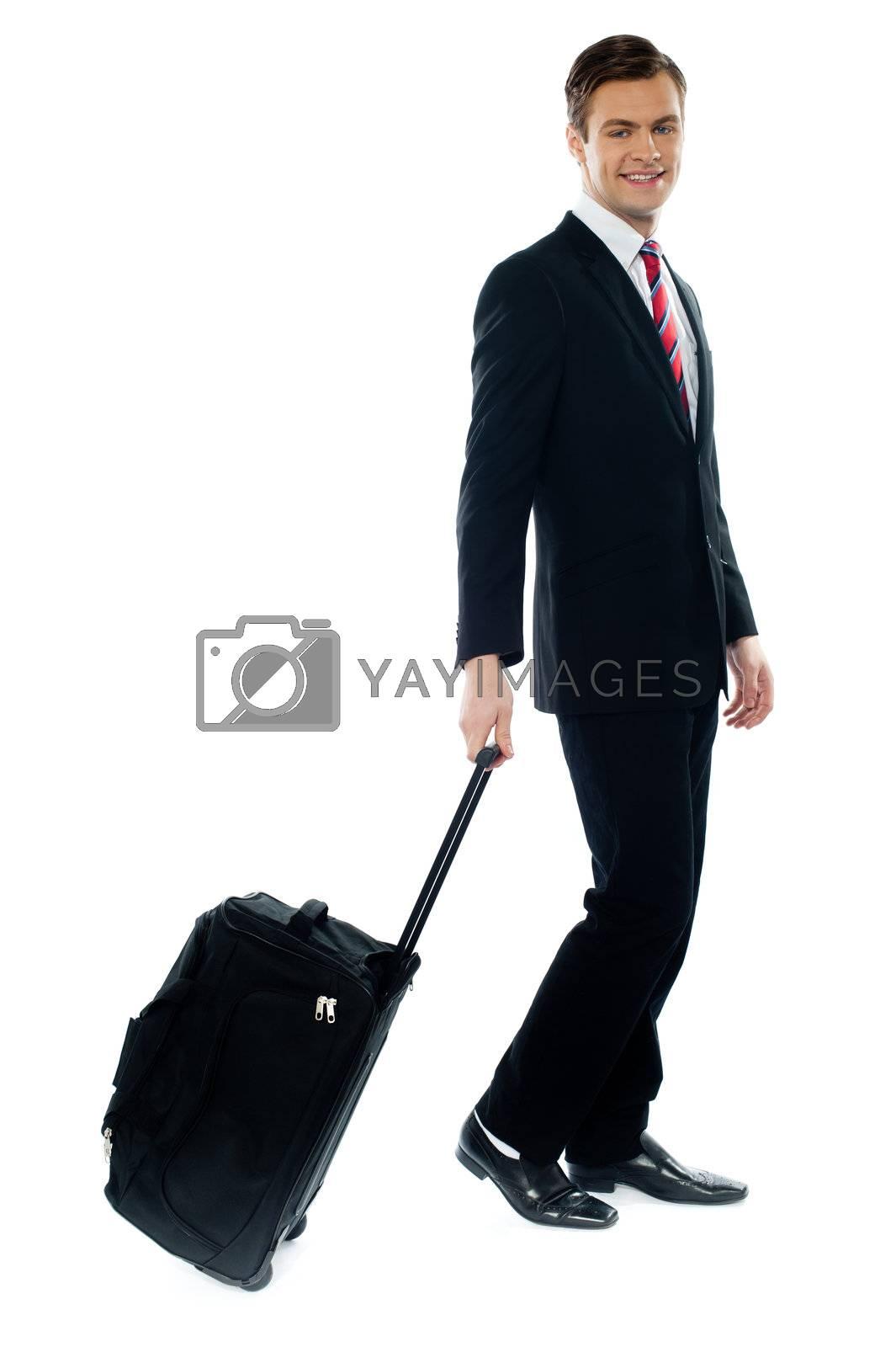Handsome businessman dragging trolley bag as he walks