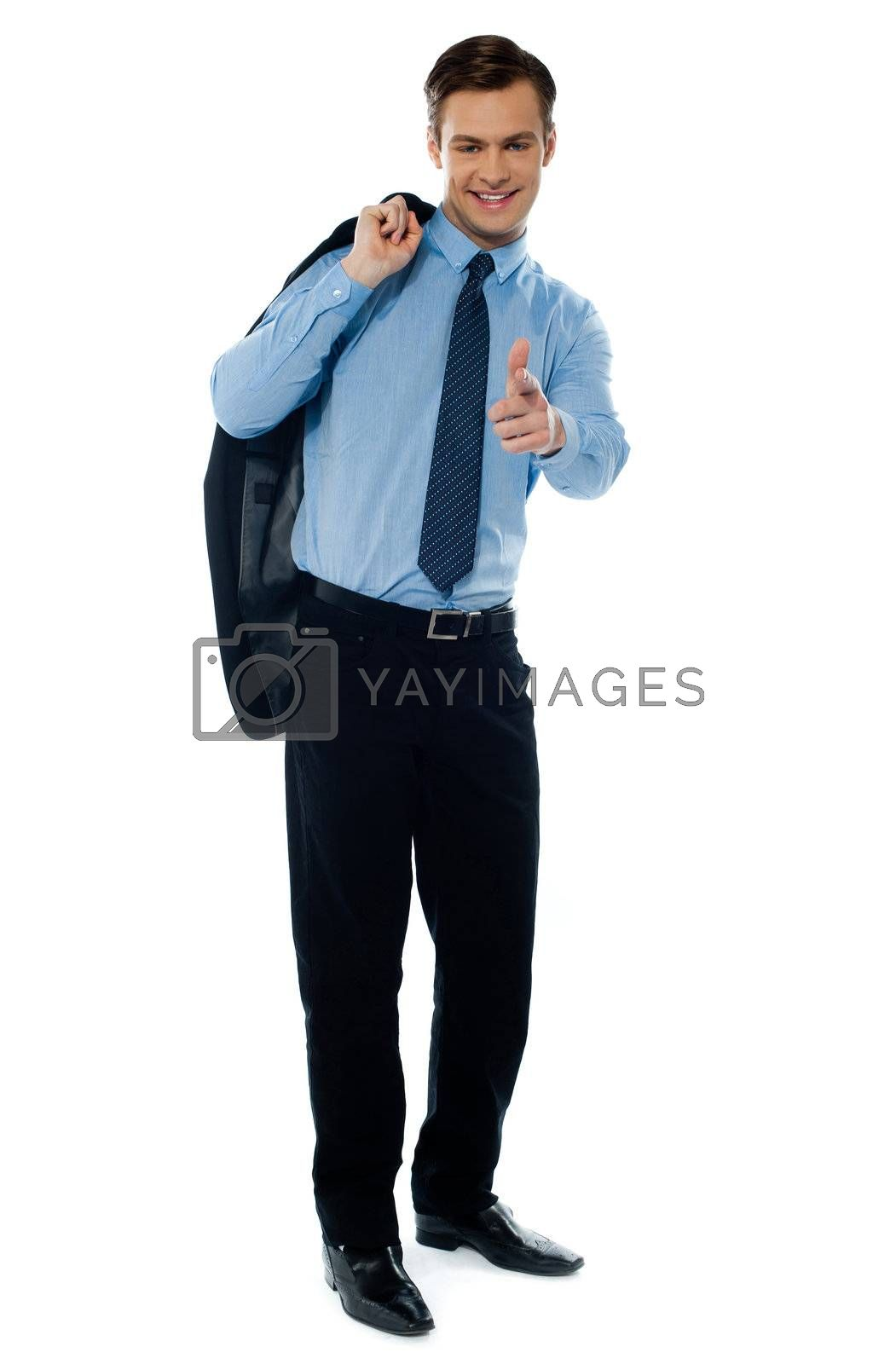 Young manager pointing towards camera on white background