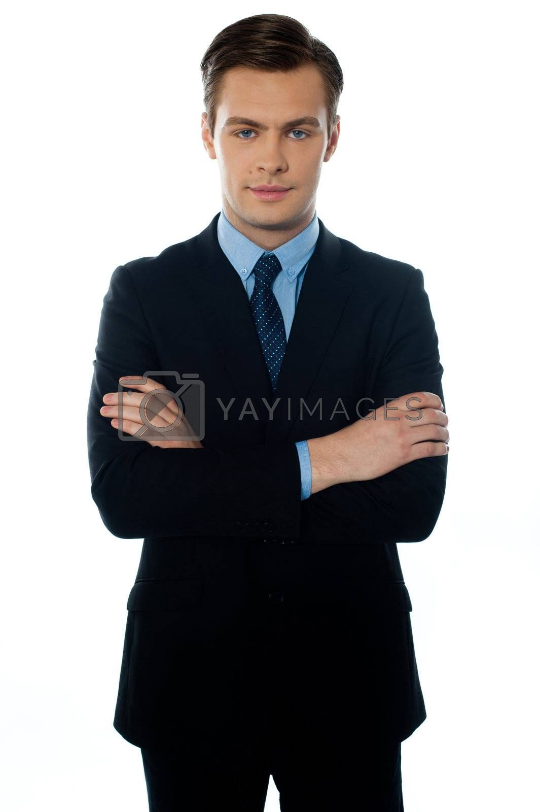Handsome young man in a business suit posing with folded arms