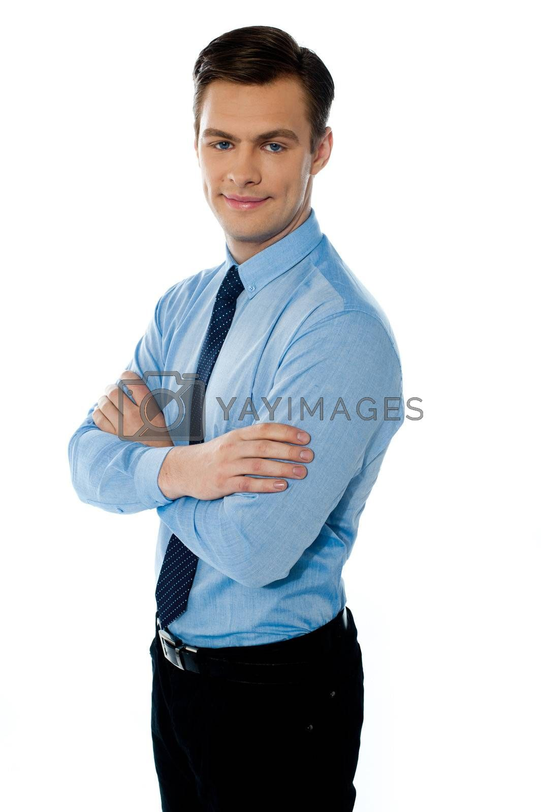 Executive standing isolated with folded hands and smiling at camera