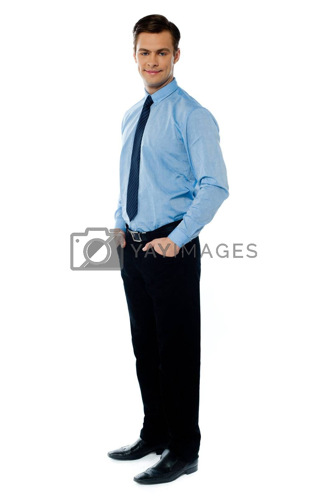 Handsome young business associate standing with hands in his pocket