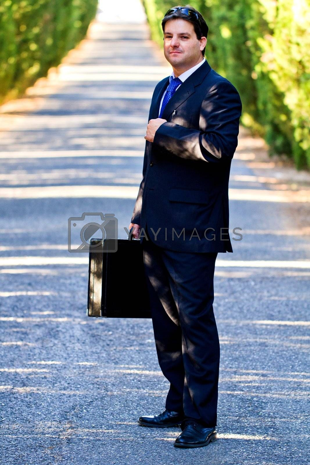 View of a young male business man on a asphalt road.