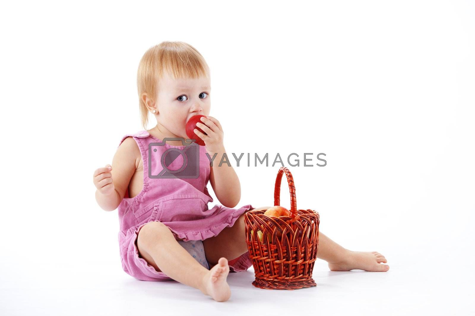 Cute toddler with apples in basket studio shot