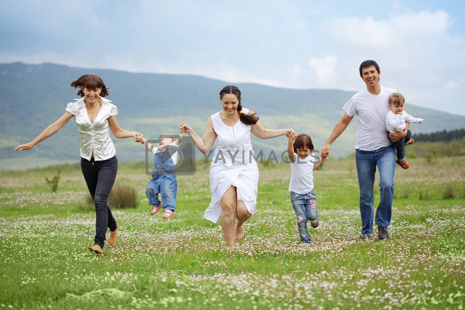 Group of happy parents with children running in field