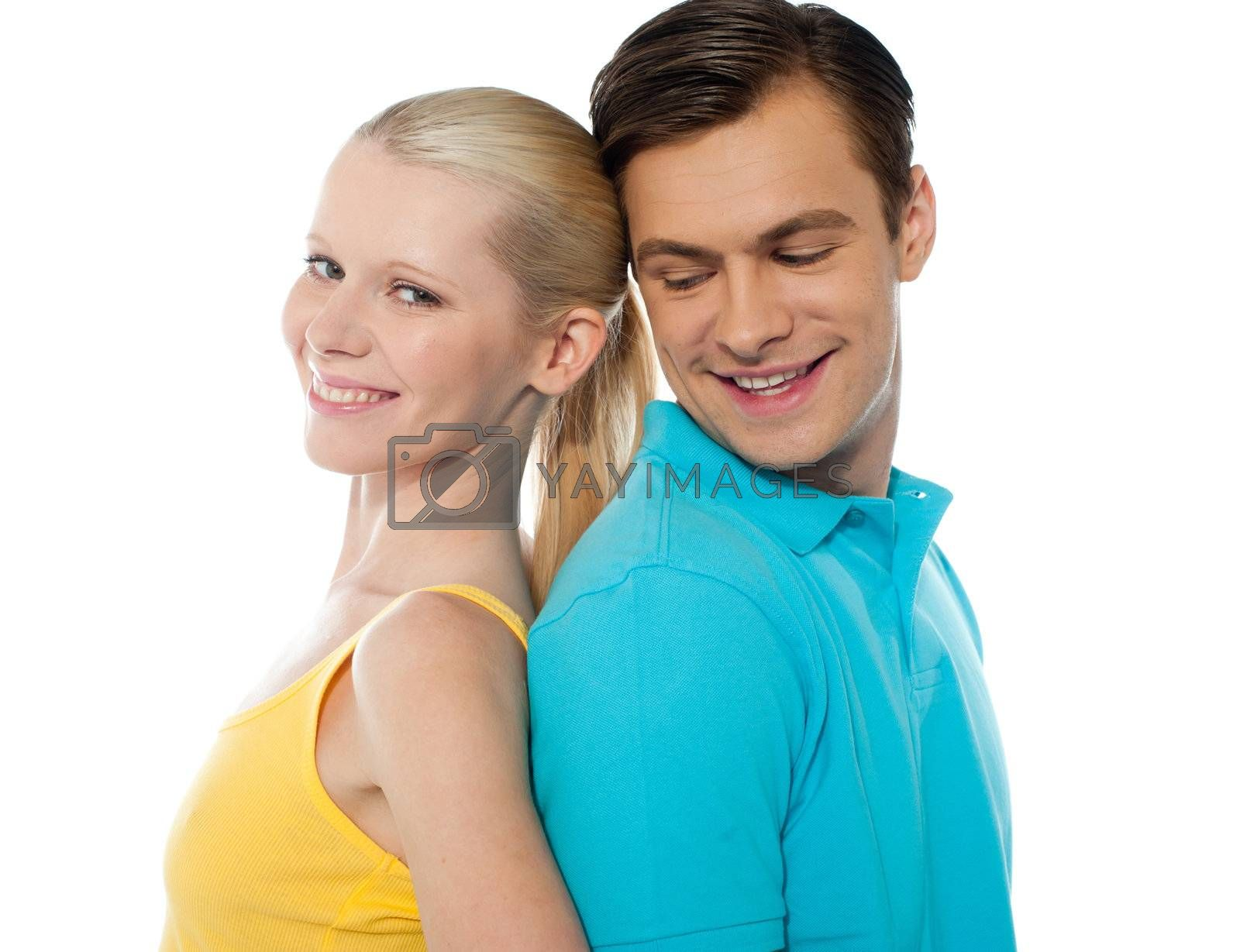 Young couple smiling and posing back to back in front of camera
