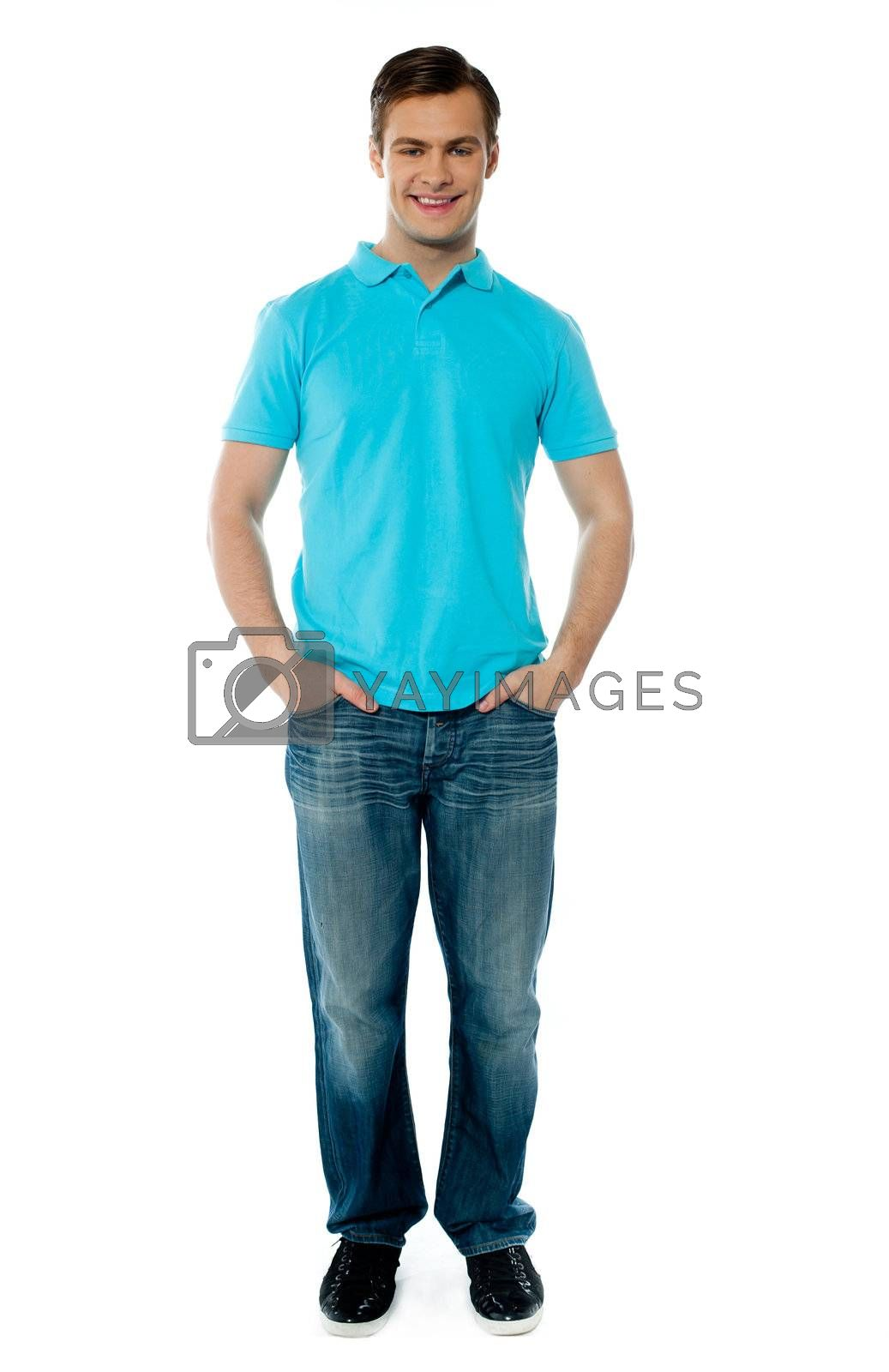 Portait of smiling cool young guy standing with arms in his pocket