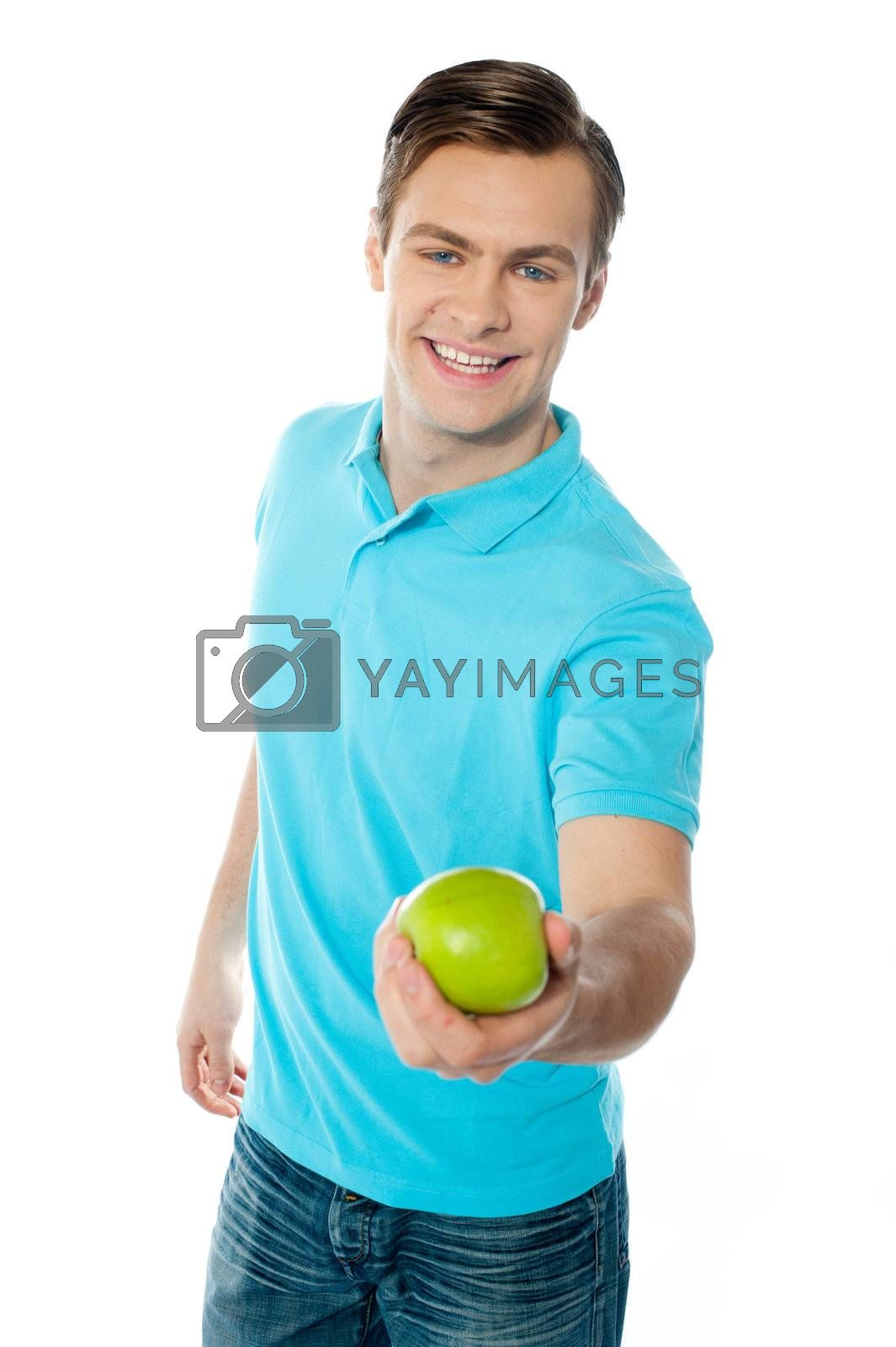 Good looking healthy guy offering a green apple isoalted over white background