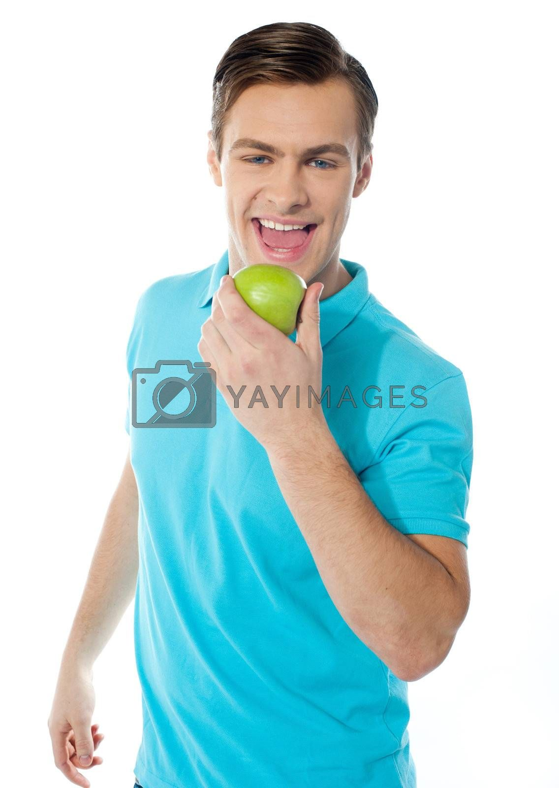 Young caucasian biting an apple on white background