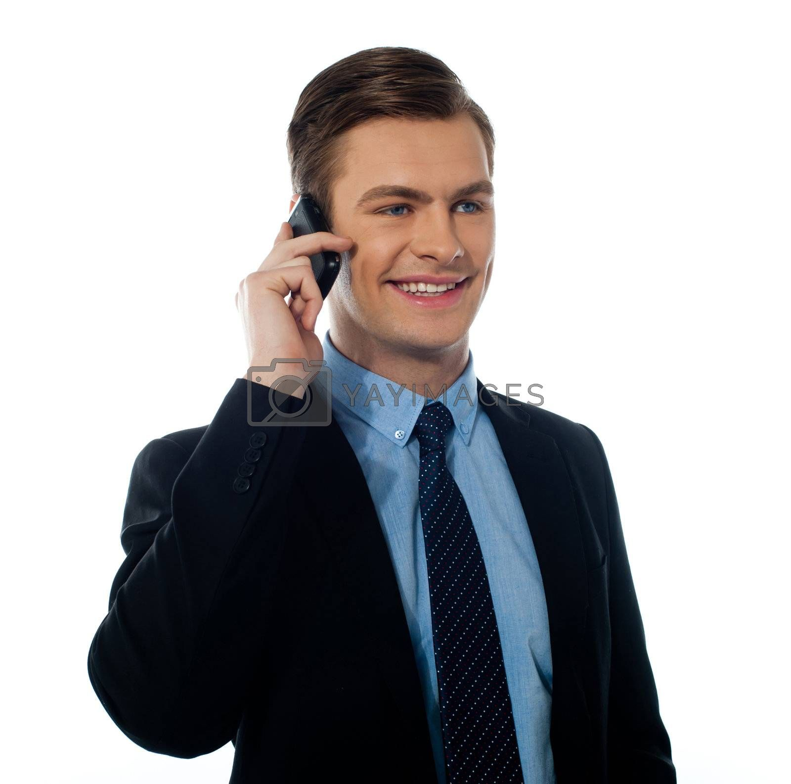 Corporate young man communicating via cell phone at work