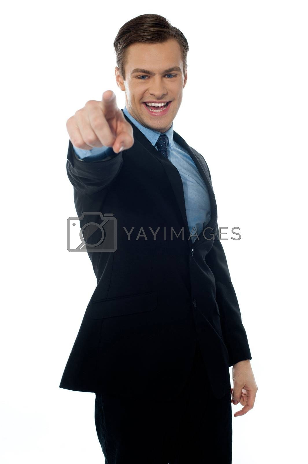 Smiling young executive pointing at you in black suit on white background
