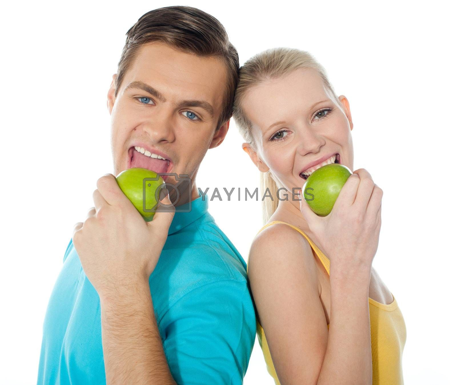 Couple posing back to back with green apples on white background