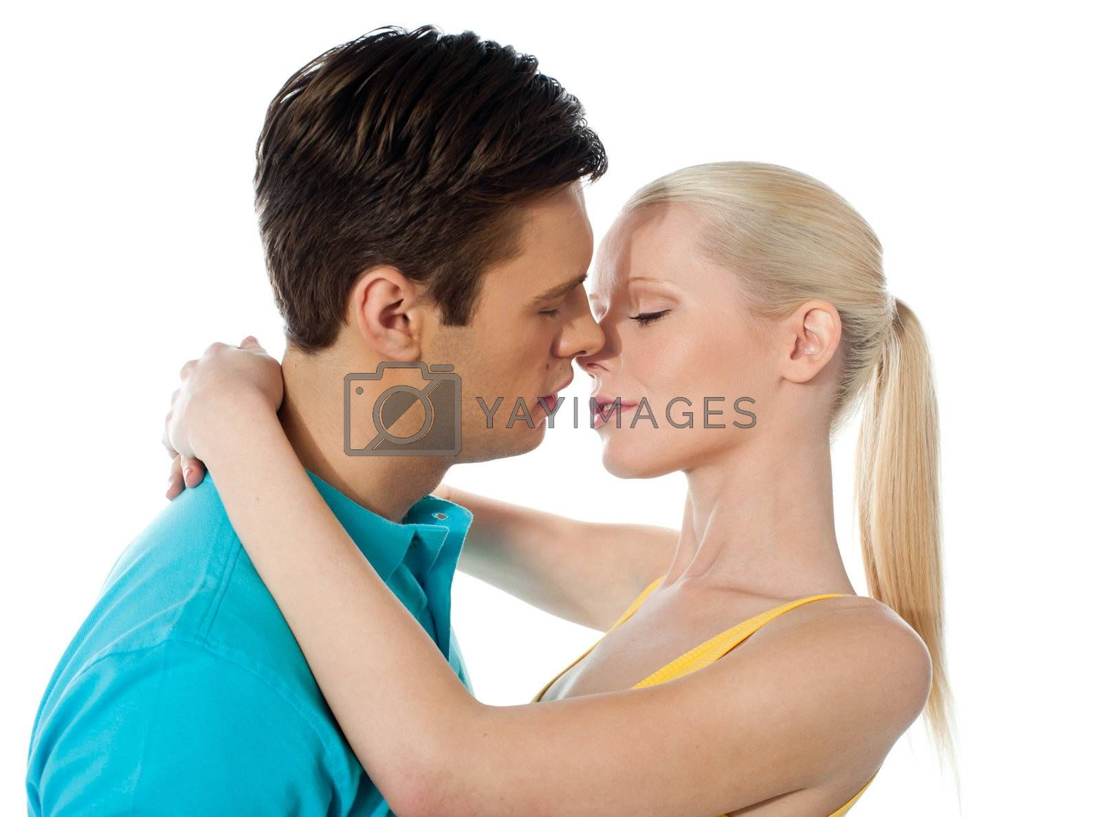 Young couple hugging and kissing on white background