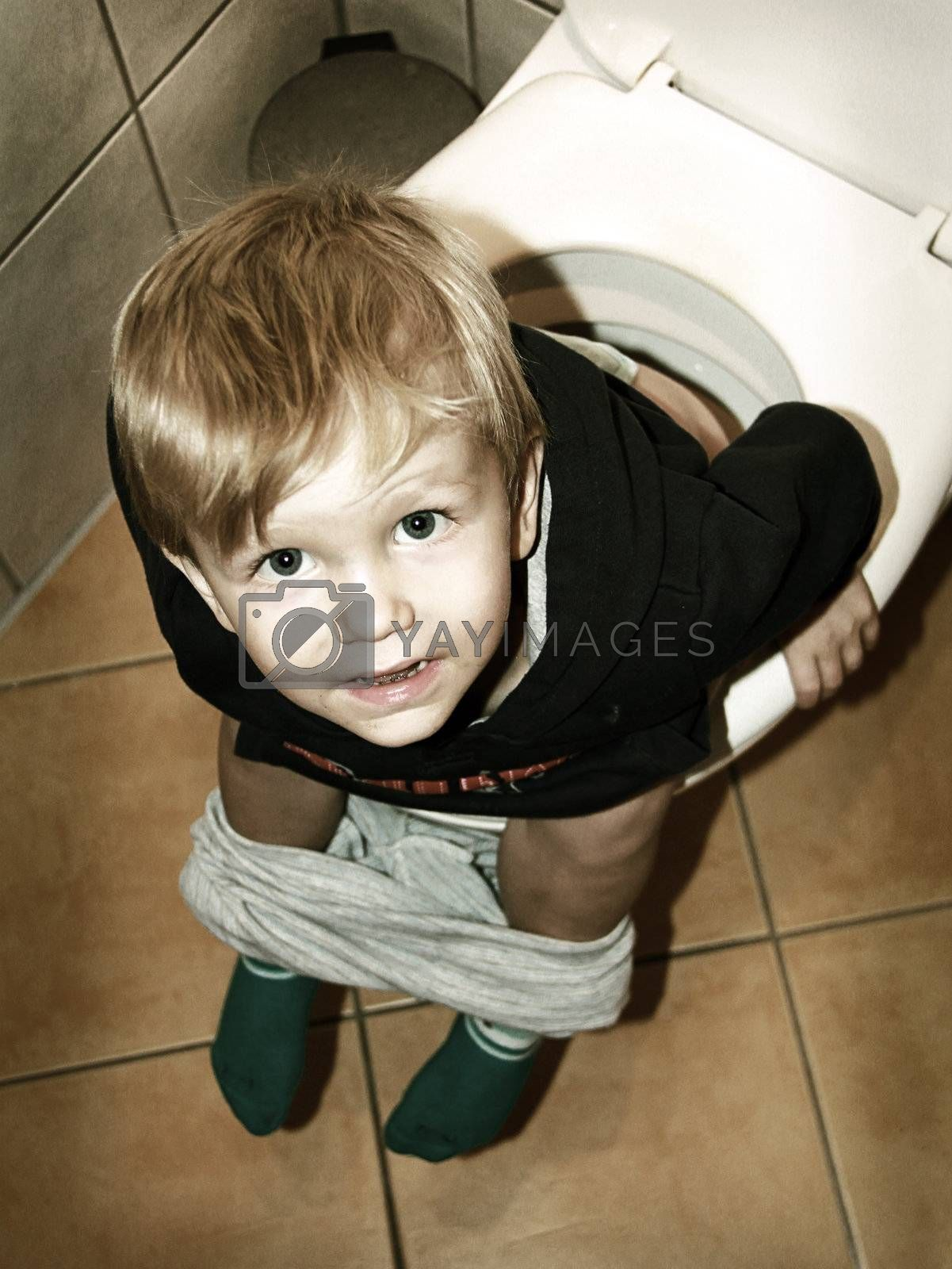 little boy is sitting on the toilet