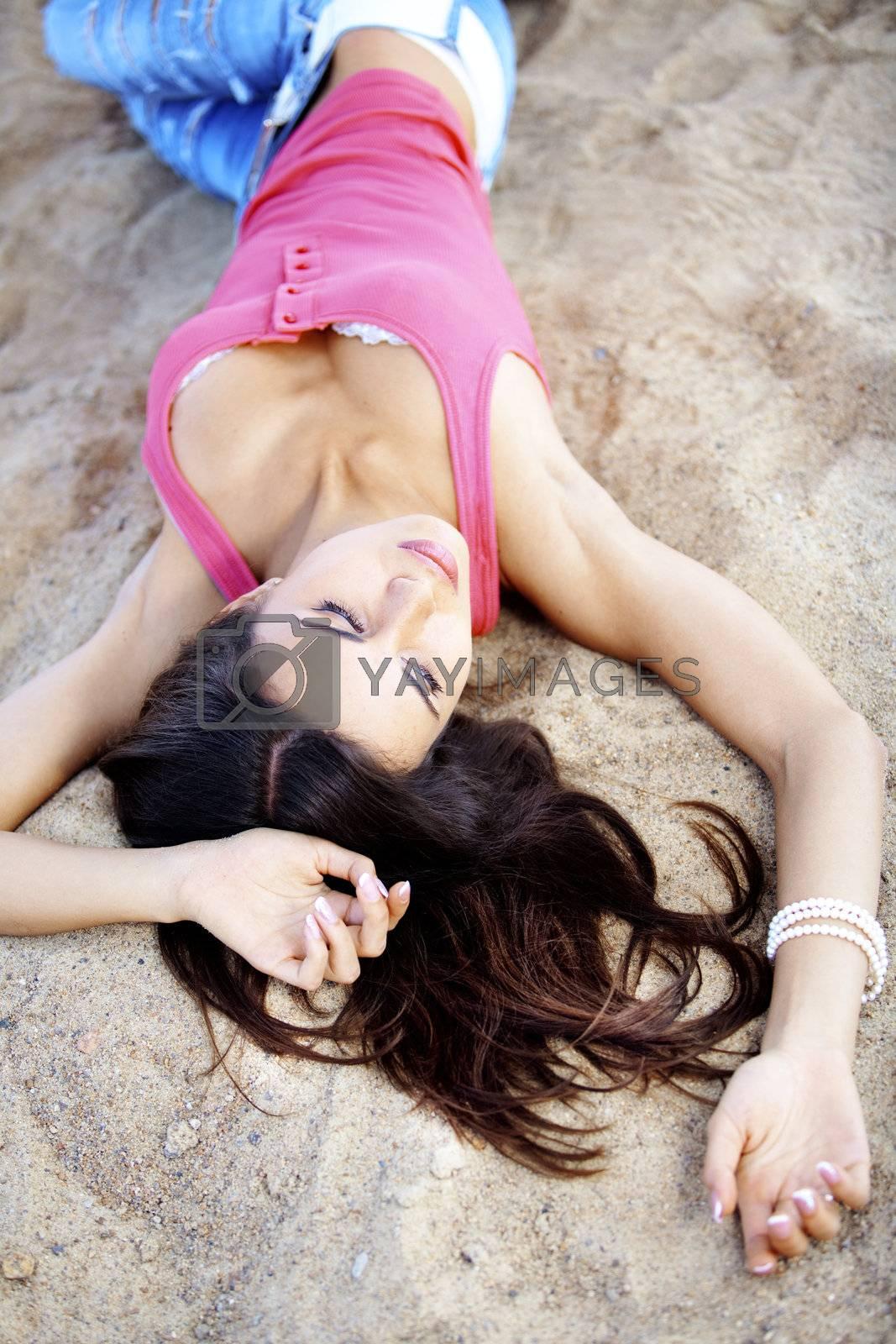 Portrait of very pretty beautiful girl lying on sand