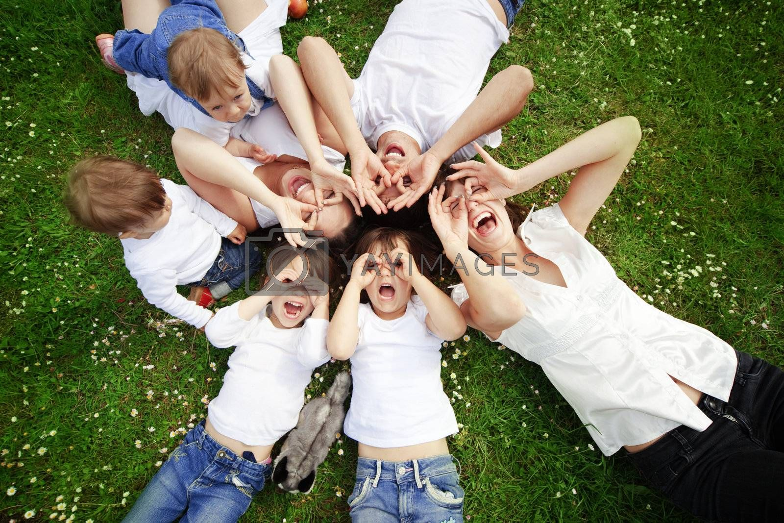 Group of happy parents with children lying on grass