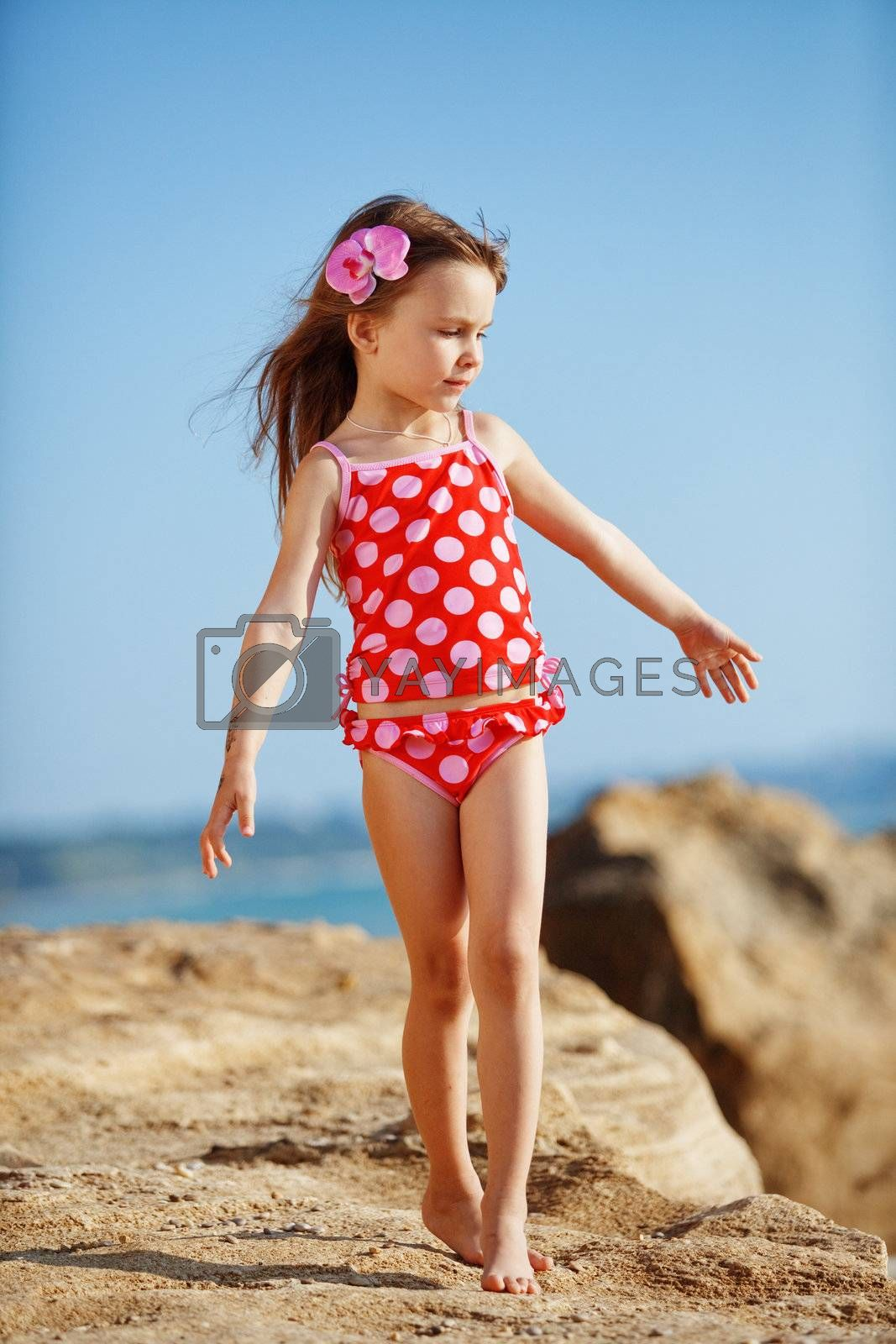 Cute child wearing swimsuit walking at beach in summer