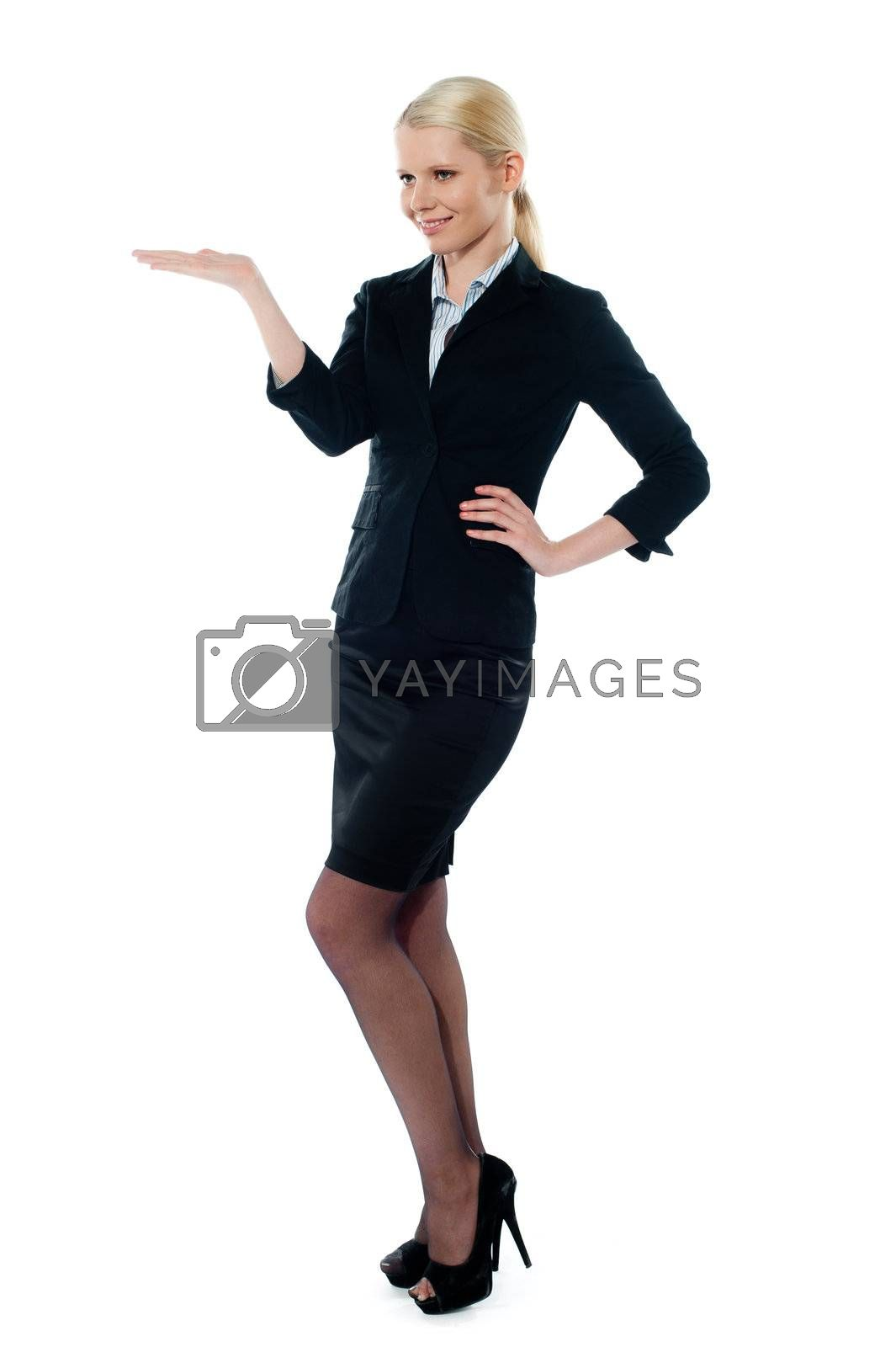 Full pose of charming young businesswoman posing with open palm and other hand on her waist