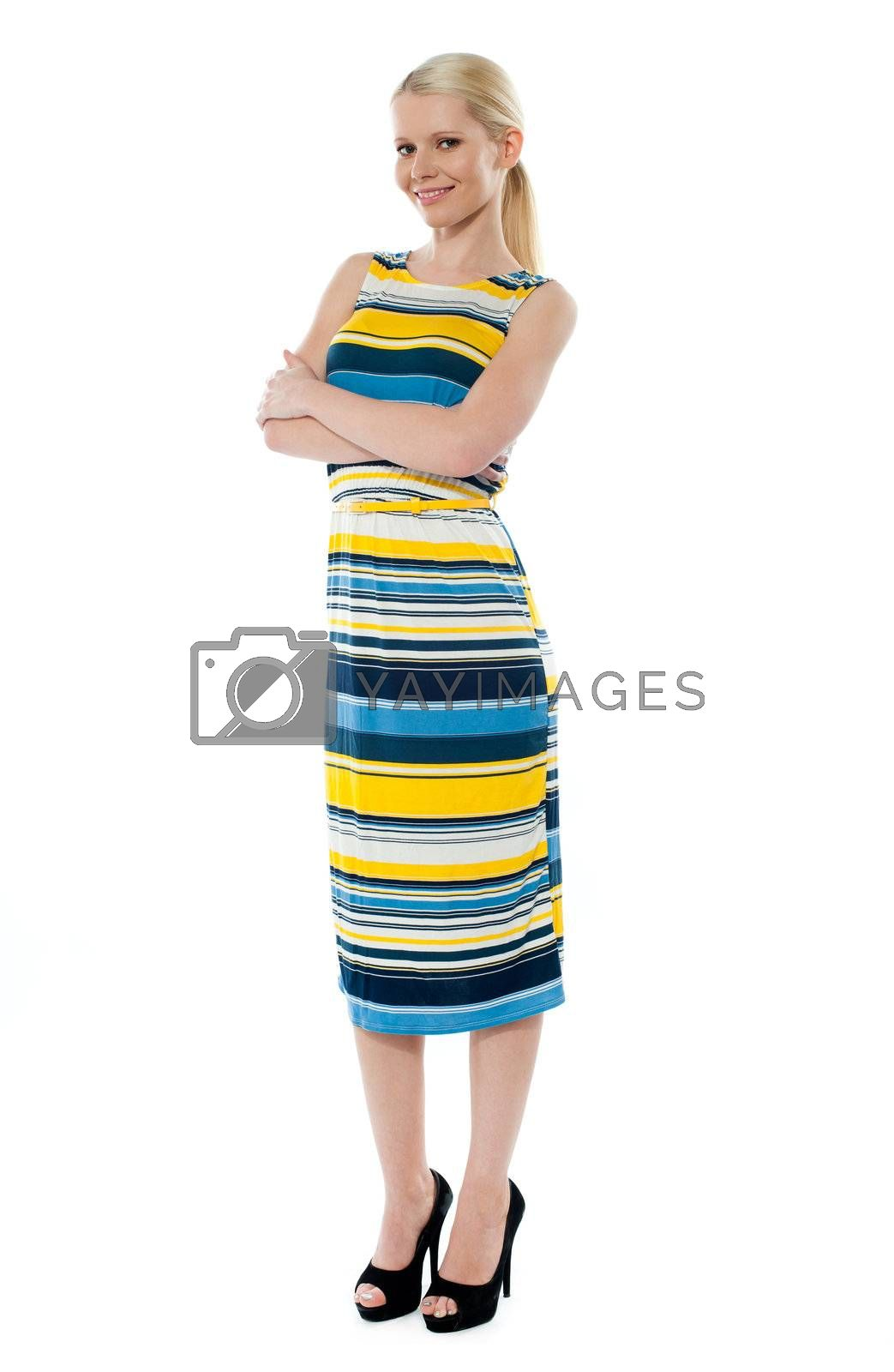Pretty girl smiling and posing with folded arms against white background