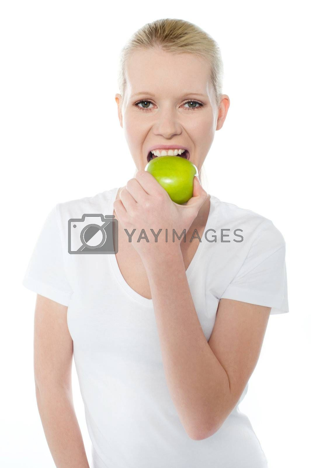 Young girl eating nutritious green apple isolated over white