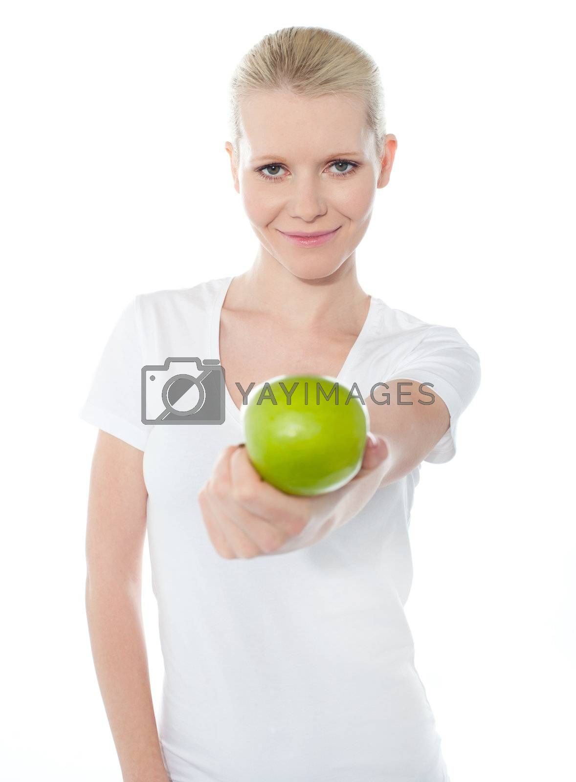 Cute teenager offering green apple dressed in white top