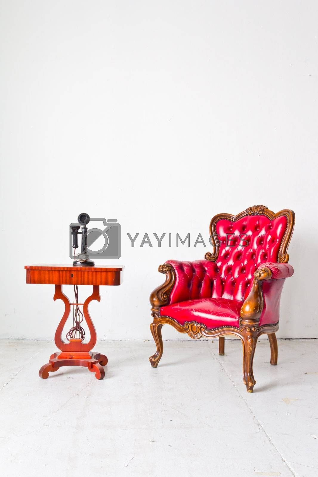 vintage red luxury armchair and telephone in white room
