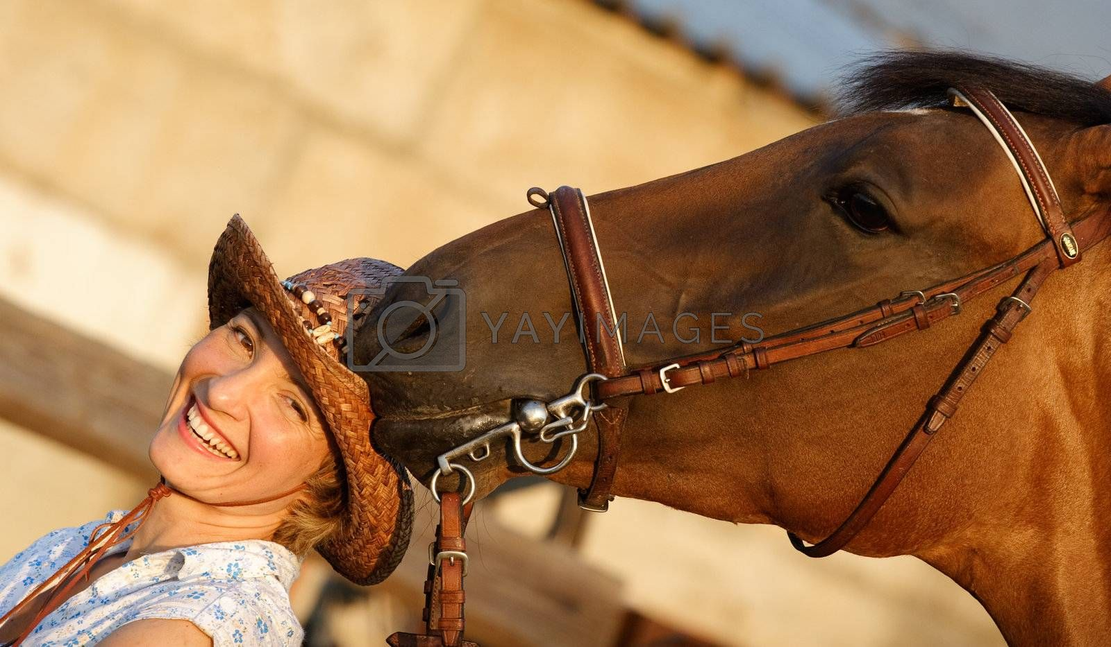 Brown horse try to eat womans hat