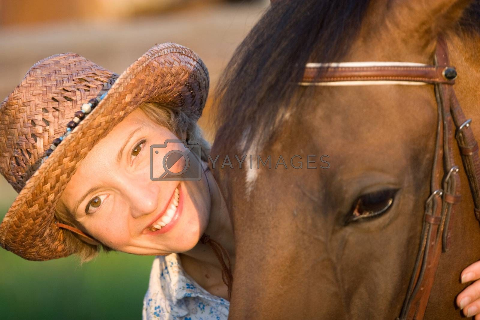 Woman in hat embrace brown horse. Close-up portrate