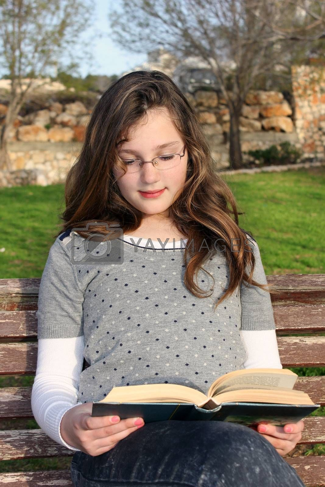 young girl with glasses, sitting in the park and reading a book