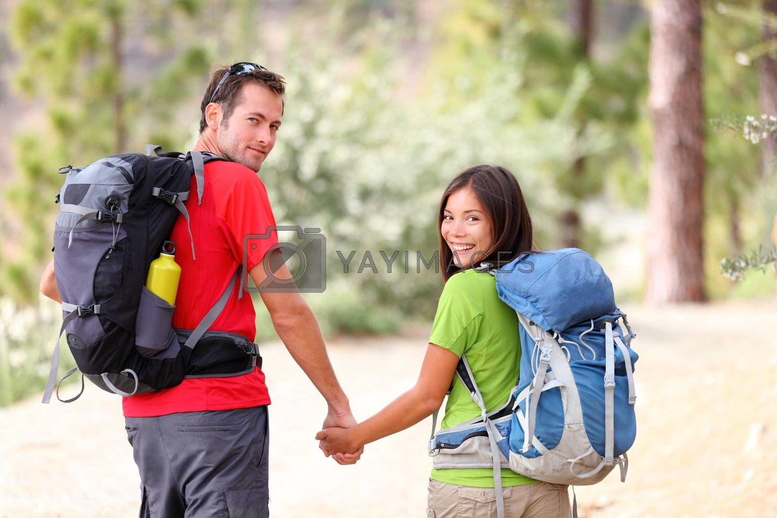 Hikers. Hiking young couple walking in forest during camping travel hike. Healthy lifestyle photo of Asian woman and Caucasian man holding hands.