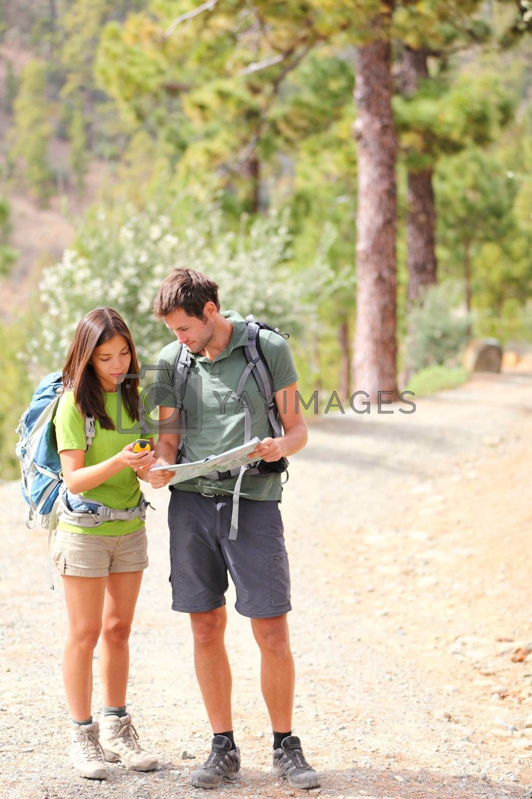 Hikers - hiking couple looking at map using GPS to navigate during camping travel hike. Young Caucasian man and Asian woman.