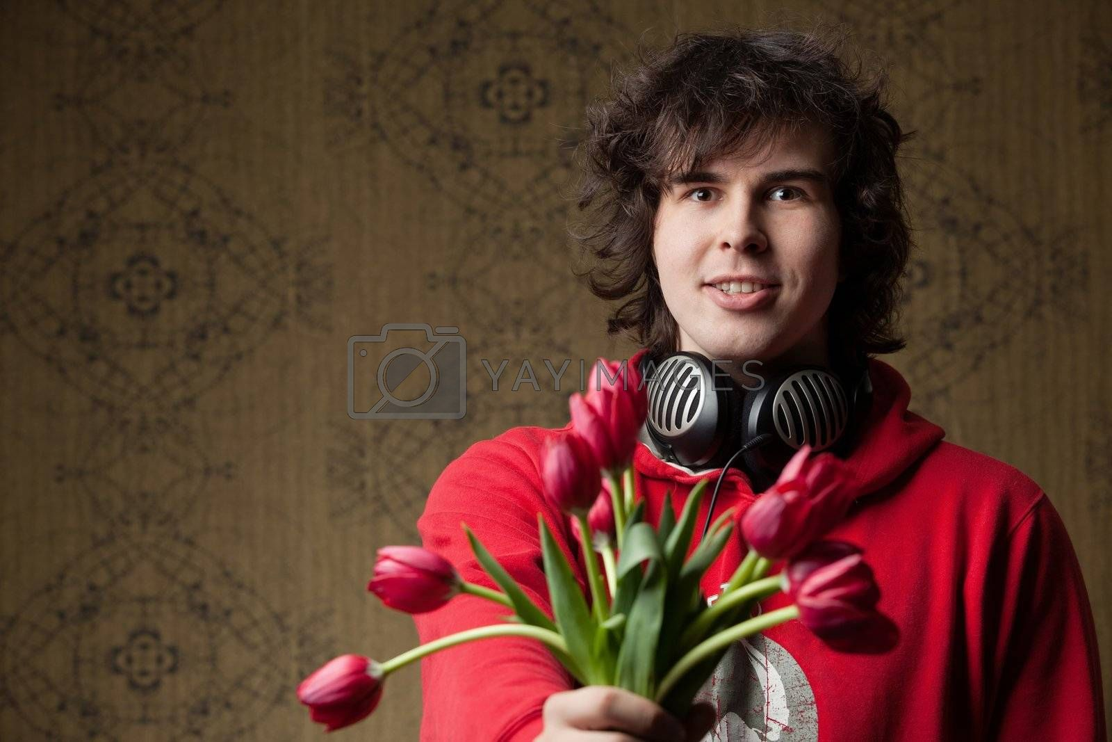 An image of a young man with red flowers