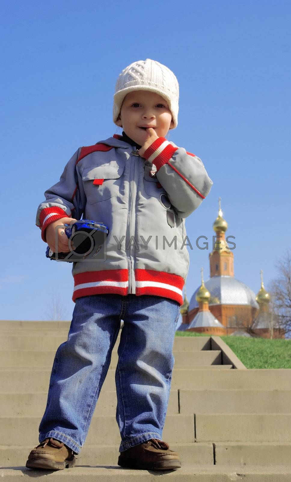 little boy in casual clothes on a walk by a sun autumn day