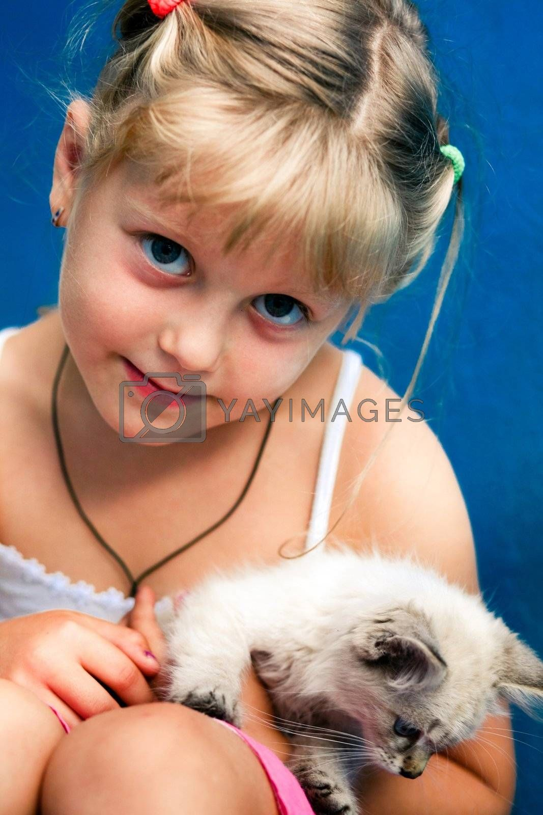 Smiling girl with a kitten in her arms