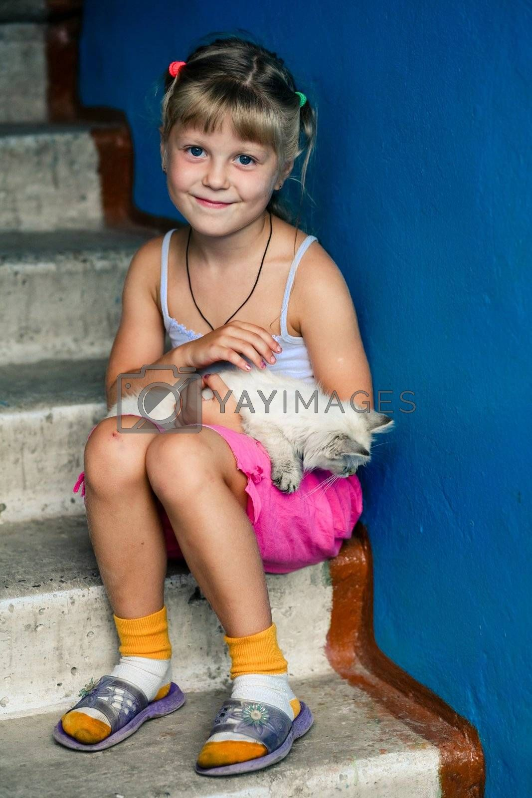 An image of smiling girl with a kitten in her arms