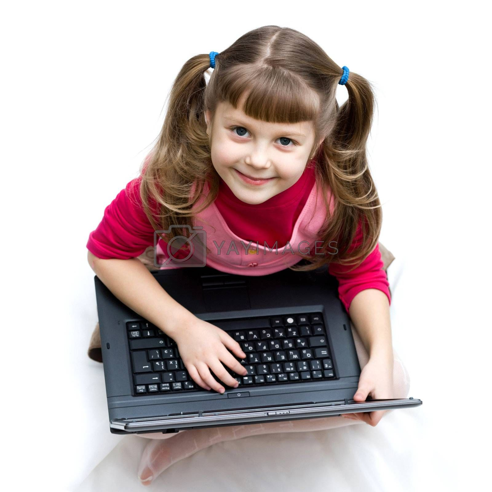 An image of a little girl with laptop sitting on the floor