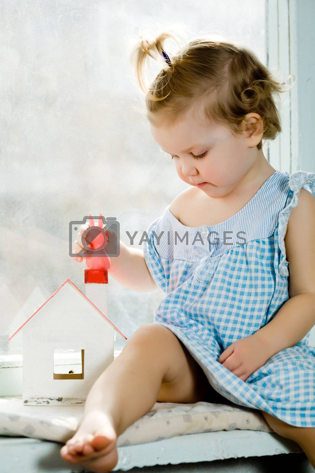 An image of a baby with little house on the window