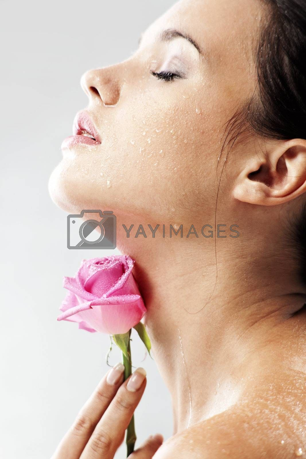 Studio portrait of sensual beautiful woman with rose and water droplets on her face