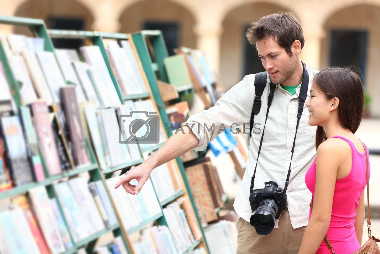 Tourist couple in Havana, Cuba looking at books together having fun on vacation travel on Plaza de Armas in Old Havana. Young travelers interracial couple, Asian woman, Caucasian man.