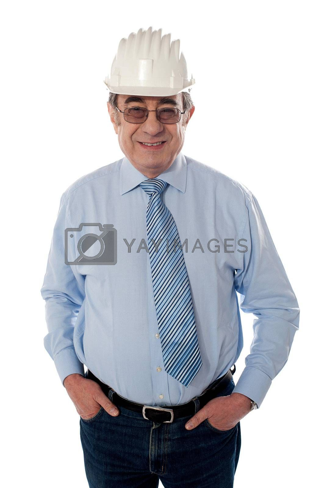 Aged builder posing with arms in pocket, smiling on white background