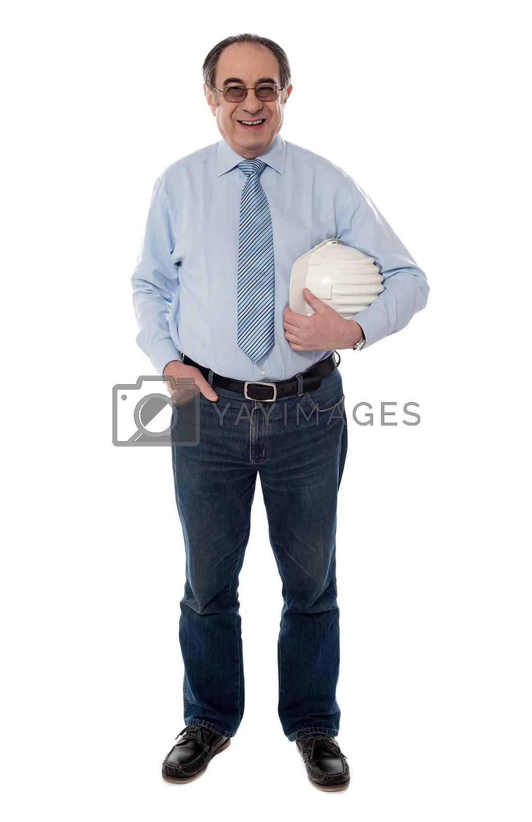 Senior architect holding helmet in one hand, full length view