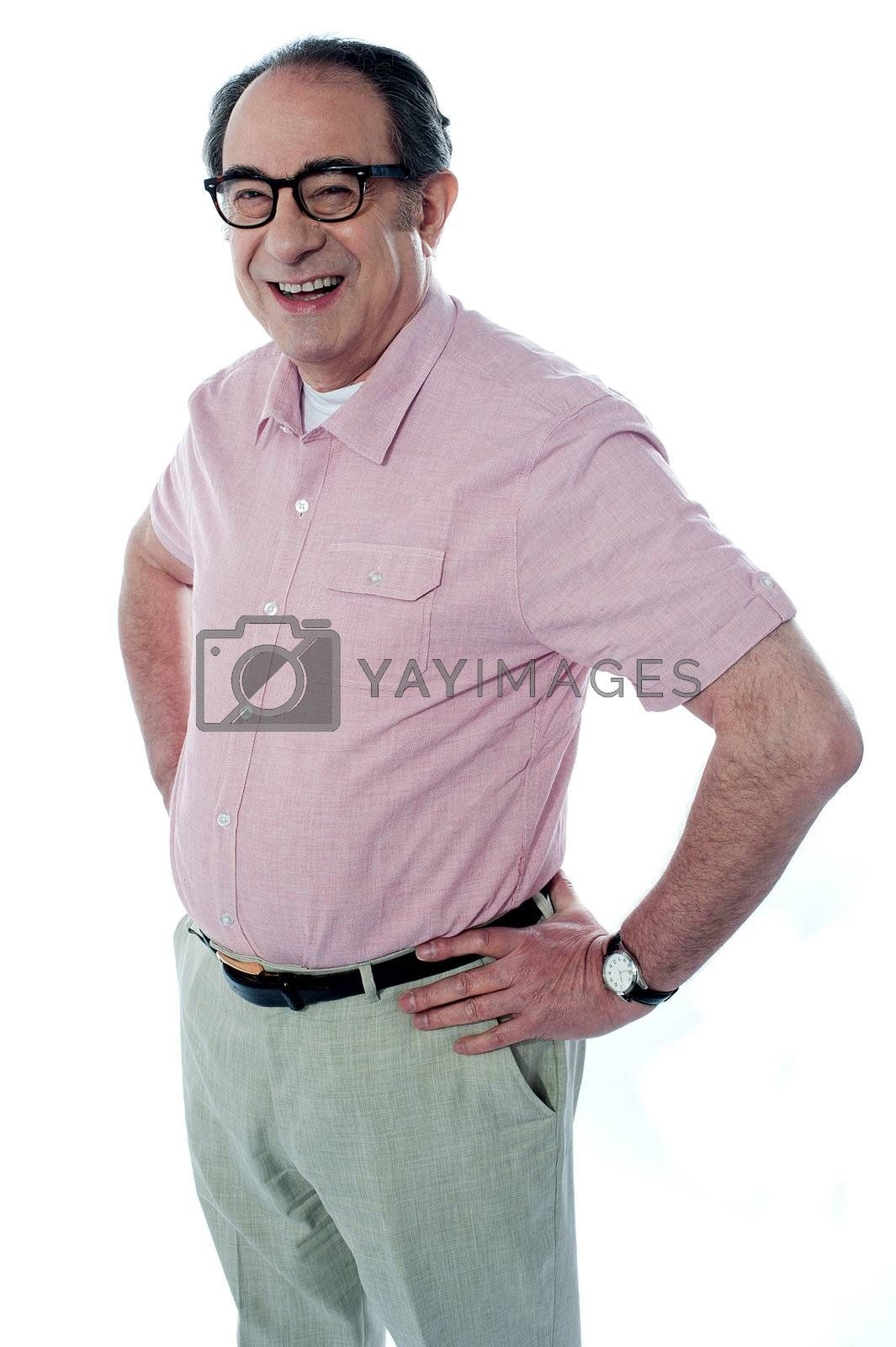 Smiling middle aged casual man standing with hands on his waist. Full length over a white background.